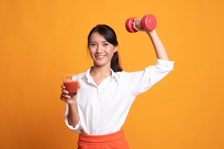 Young healthy Asian woman with dumbbell and  tomato juice on yellow background
