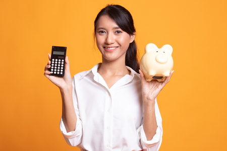 Asian woman with calculator and piggy bank on yellow background