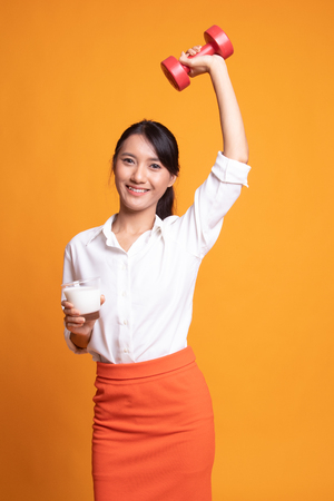 Healthy Asian woman drinking a glass of milk and dumbbell on yellow background