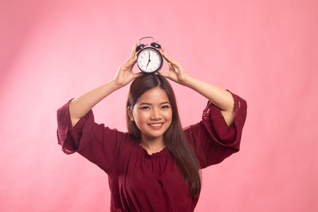 Young Asian woman smile with a clock on pink background