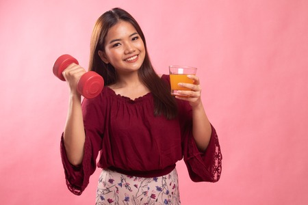 Young Asian woman with dumbbell drink orange juice on pink background