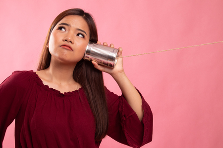 Young Asian woman with tin can phone on pink background