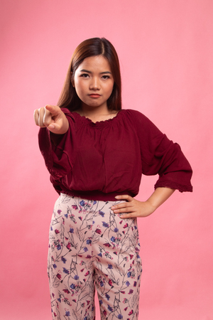 Young Asian woman angry and point to camera on pink background Stock Photo