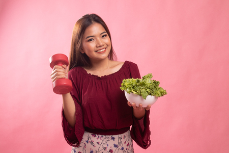 Healthy Asian woman with dumbbells and salad on pink background Banco de Imagens