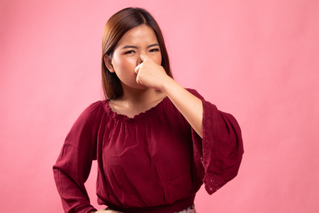 Young Asian woman  holding her nose because of a bad smell on pink background Imagens