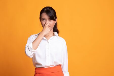 Young Asian woman  holding her nose because of a bad smell on yellow background