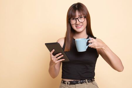 Young Asian woman with a computer tablet and coffee  on beige background Banco de Imagens