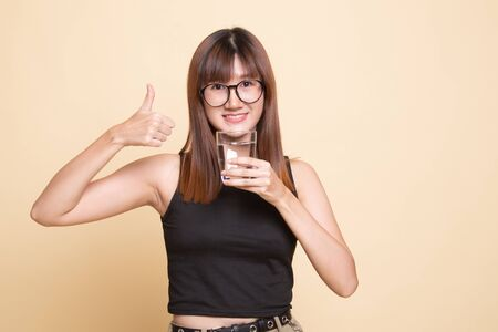 Young Asian woman thumbs up with a glass of drinking water  on beige background