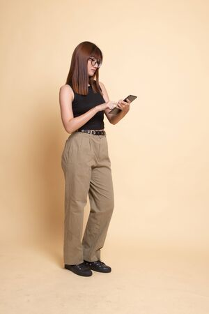 Full body of young Asian woman with a computer tablet  on beige background Banco de Imagens