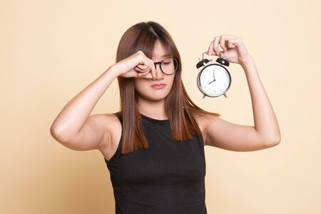 Sleepy young Asian woman with a clock in the morning  on beige background 写真素材