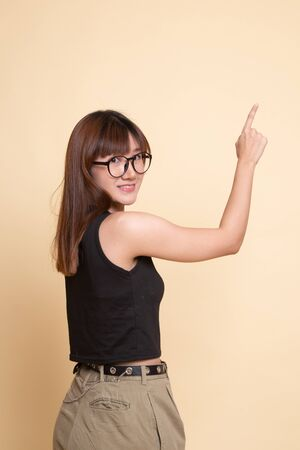Back of Asian woman touching the screen with her finger  on beige background