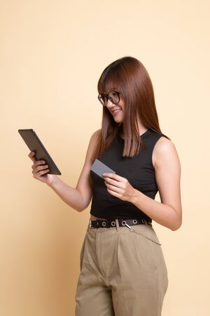Young Asian woman is shopping online with credit card and tablet  on beige background