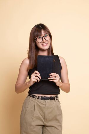 Young Asian woman with a computer tablet  on beige background