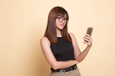 Young Asian woman with mobile phone  on beige background Banco de Imagens