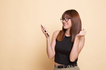Happy Young Asian woman with mobile phone  on beige background