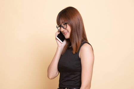 Young Asian woman talking with mobile phone  on beige background
