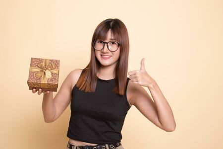 Asian woman thumbs up with a gift box on beige background