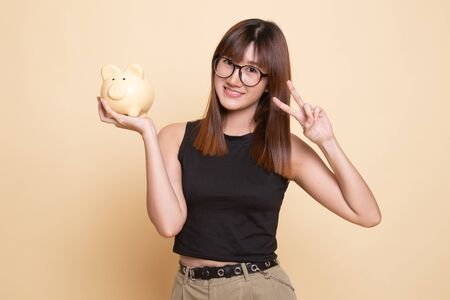 Asian woman show victory sign with pig coin bank  on beige background Фото со стока