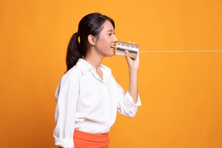 Young Asian woman with tin can phone on yellow background