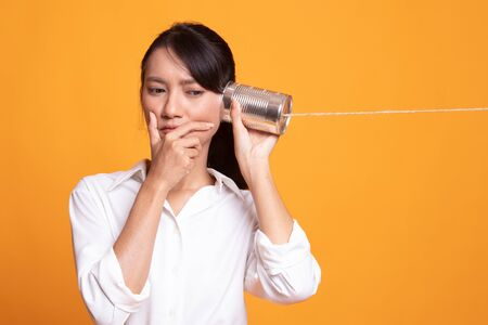 Young Asian woman hearing with tin can phone and thinking on yellow background