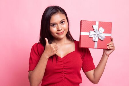 Young Asian woman thumbs up with a gift box on pink background