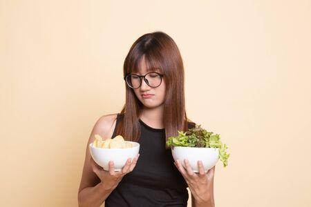 Junge asiatische Frau mit Kartoffelchips und Salat auf beigem Hintergrund