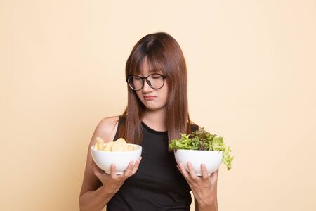 Young Asian woman with potato chips and salad  on beige background