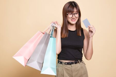 Young Asian woman with shopping bag and blank card  on beige background