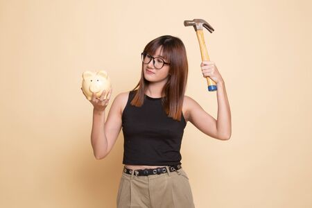 Asian woman with pig coin bank and hammer  on beige background Banco de Imagens