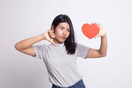 Asian woman thumbs down with red heart on white background