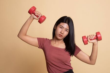 Exhausted Asian woman with dumbbells on beige background 版權商用圖片
