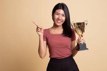 Successful young asian woman holding a trophy point to blank space on beige background