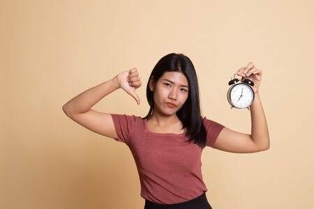 Young Asian woman thumbs down with a clock on beige background