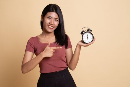 Young Asian woman point to a clock on beige background