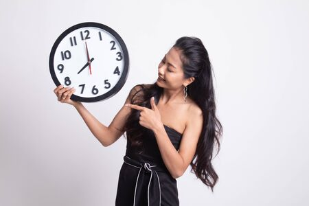 Young Asian woman point to a clock on white background