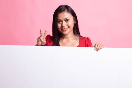 Young Asian woman show victory sign with blank sign on pink background
