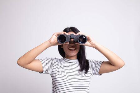 Joven asiática con binoculares sobre fondo blanco.