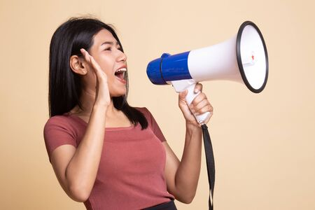 Beautiful young Asian woman announce with megaphone on beige background Stockfoto