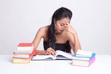 Exhausted Asian woman got headache read a book with books on table on white background