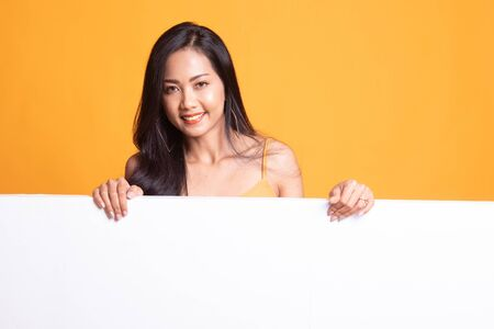 Young Asian woman with blank sign on yellow background 版權商用圖片