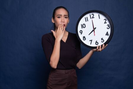 Sleepy young Asian woman with a clock in the morning on blue background 写真素材