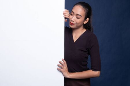 Young Asian woman with blank sign on blue background 版權商用圖片