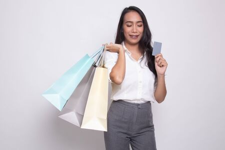 Young Asian woman with shopping bag and blank card on white background Banco de Imagens