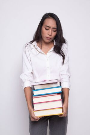 Unhappy young Asian woman carrying books