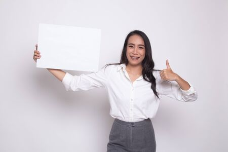 Young Asian woman show thumbs up with  white blank sign on white background Banco de Imagens