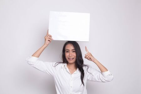 Young Asian woman point to blank sign on white background
