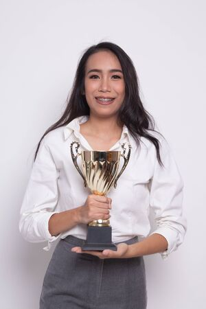 Successful young asian woman holding a trophy on white background Banco de Imagens