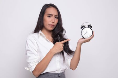 Angry young Asian woman point to a clock on white background Imagens