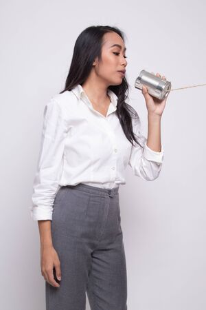 Young Asian woman with tin can phone on white background