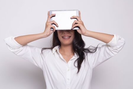 Young Asian woman with a computer tablet over her face on white background